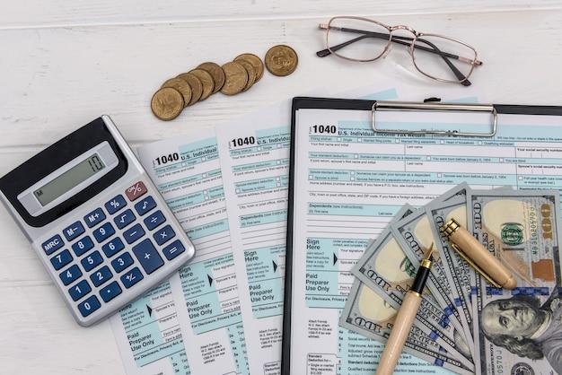 Formulario de impuestos con dólares y gafas y calculadora.