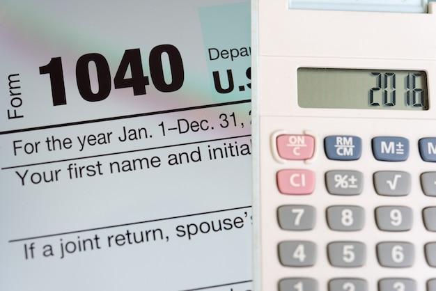 Formulario de impuestos en la pantalla de la tableta y la calculadora