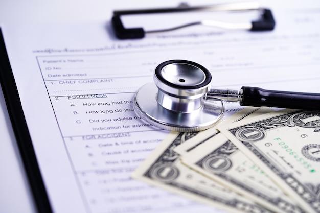 Formulario de reclamo de accidente de seguro de salud con estetoscopio y billetes de dólares estadounidenses.
