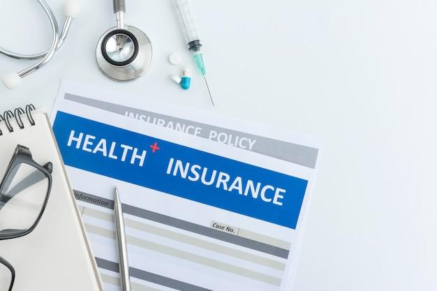 Formulario de seguro de salud con estetoscopio en vista superior