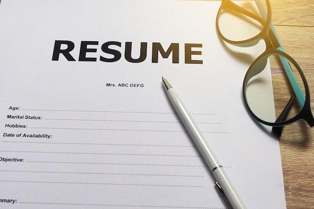 Formulario de solicitud de empleo tenga bolígrafos y anteojos.