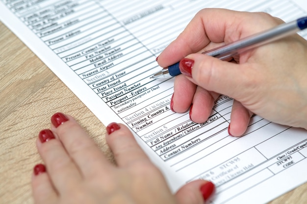 Formulario de solicitud mano sosteniendo el bolígrafo listo para completar una lista de preguntas formulario de solicitud