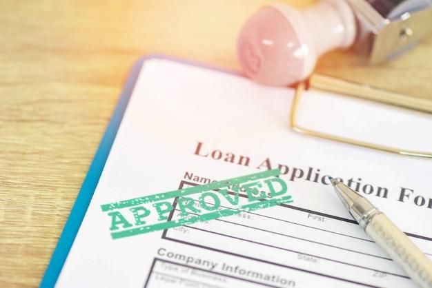 Formulario de solicitud de préstamo con sello de goma que dice préstamo aprobado, aprobación de préstamo financiero