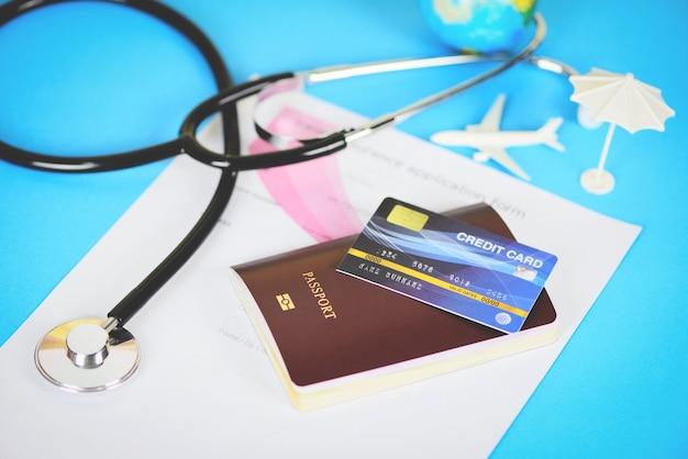 Formulario de solicitud de seguro de viaje con pasaporte, tarjeta de crédito y estetoscopio
