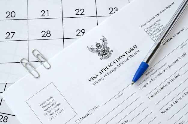 Formulario de solicitud de visa de tailandia y bolígrafo azul en la página de calendario de papel