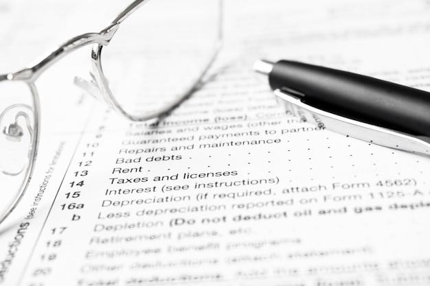 Formulario w9 de las leyes federales de impuestos sobre la renta. bolígrafo y anteojos