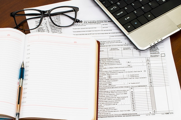 Formularios de impuestos con los anteojos, el dinero y la pluma