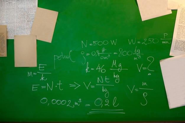 Fórmulas matemáticas y papeles en una pizarra verde - concepto de pizarra y escuela. enseñanza de la física