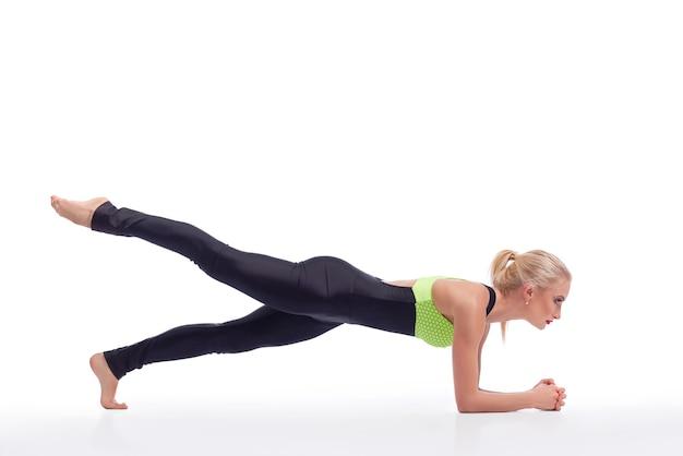 Fortaleciendo su núcleo. mujer deportiva haciendo ejercicio de tablazón en el estudio aislado copyspace arriba