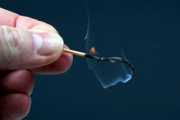 Fósforo de madera ardiendo y fumando en la mano sobre fondo oscuro