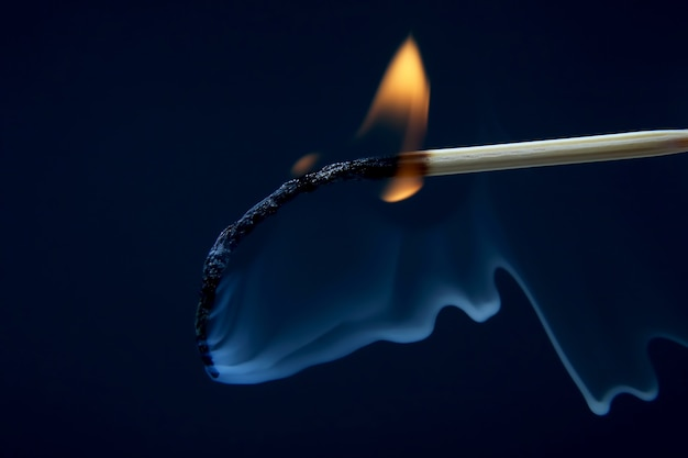 Fósforo de madera ardiendo y fumando sobre fondo oscuro