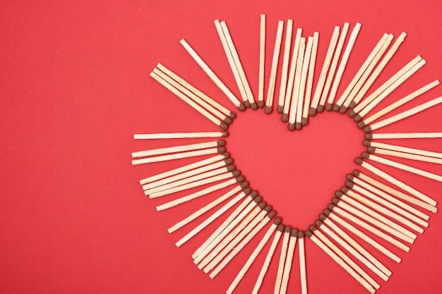 Fósforos en forma de corazón sobre rojo