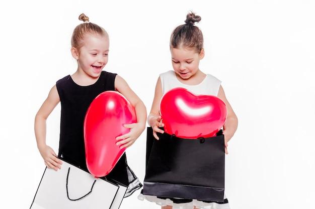 Foto de 2 niñas con vestidos elegantes que sostienen bolsas grandes con globos en forma de corazón en el interior