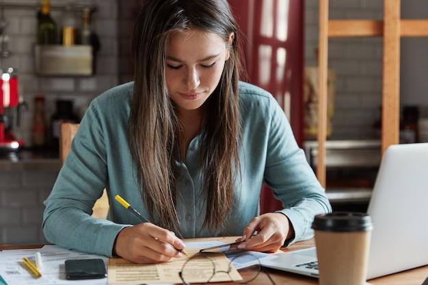 La foto de la abogada anota el número de la tarjeta de presentación en documentos, se sienta en el escritorio con computadora portátil, teléfono móvil y documentos