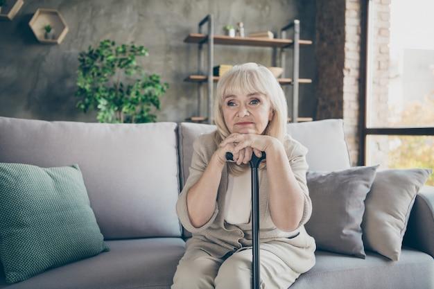 Foto de abuela anciana de pelo blanco sosteniendo bastón sufre solo en gran piso mirando desesperada soledad ojos sentados diván sofá sala de estar apartamentos en el interior