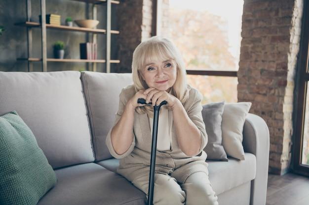 Foto de abuela de pelo blanco sosteniendo bastón recordando la luz de la juventud tristeza recuerdos románticos falta marido sentado diván sofá sala de estar apartamentos en el interior