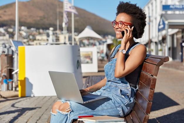 Foto de un adolescente afroamericano sonriente y alegre que llama a alguien a través de un teléfono celular, mantiene la computadora portátil sobre las rodillas, se sienta en un banco al aire libre y usa aparatos para estudiar en línea, blogs moda, estilo de vida, tecnología