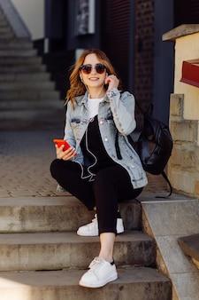 Foto de una adolescente alegre positiva pasa tiempo en el parque y usando el teléfono móvil.