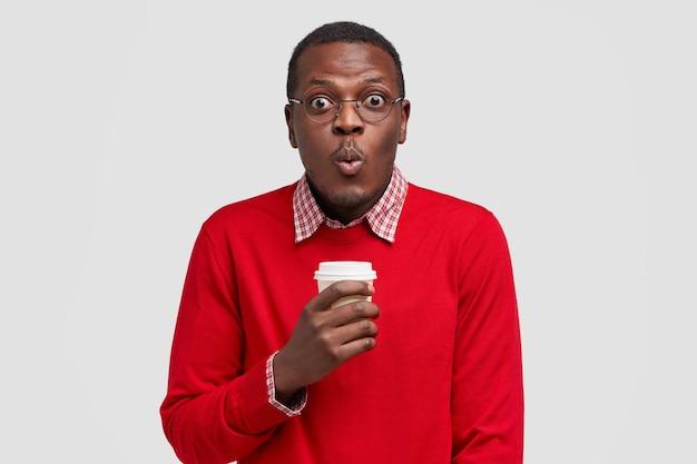 Foto de adolescente estupefacto con piel negra, se sorprende al escuchar noticias impactantes, sostiene café aromático para llevar