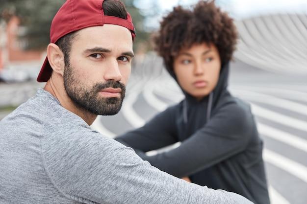 Foto de adolescentes con estilo hipster pasan tiempo libre al aire libre, miran pensativamente en algún lugar