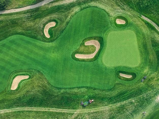 Foto aérea del club de golf, césped verde, árboles, carreteras, cortadoras de césped, endecha plana