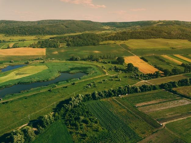 Foto aérea de drone con hermoso paisaje farmlamnd al atardecer en atmósfera rural