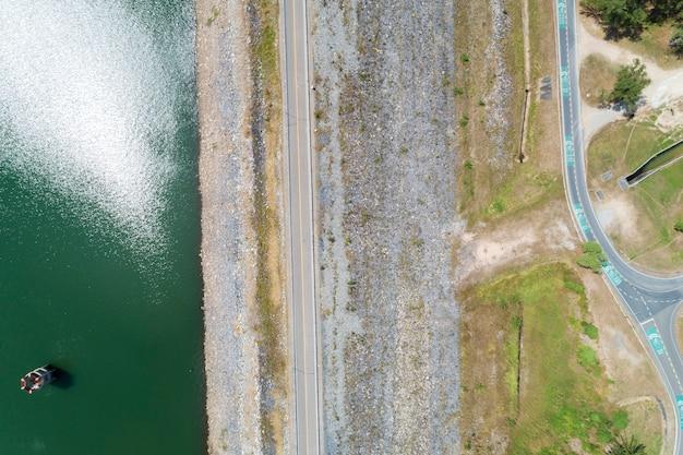 Foto aérea del drone volador de la carretera asfaltada y del carril para bicicletas alrededor de la presa