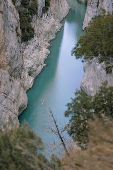Foto aérea de un kayak en un río entre montañas