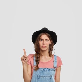 La foto de una agricultora disgustada viste un mono informal, un elegante sombrero negro, señala en la esquina superior, se siente insatisfecha con la nueva compra, expresa su disgusto, nota algo inútil e inútil