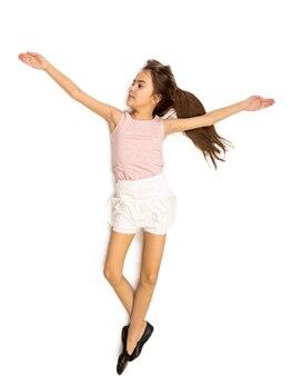 Foto aislada de linda niña sonriente en falda haciendo ballet pas