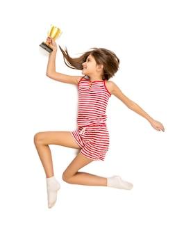 Foto aislada desde el punto de vista alto de la niña activa feliz corriendo con trofeo de oro