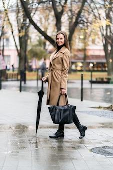 Foto al aire libre de una dama morena posando con paraguas negro en un día lluvioso de otoño. retrato de estilo callejero de moda. vistiendo pantalones casuales oscuros, suéter blanco y abrigo color crema. concepto de moda.