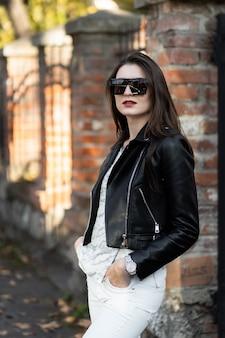 Foto al aire libre de la dama morena sentarse en la valla en día de otoño. retrato de estilo callejero de moda. chica vestida con pantalón blanco, camiseta, chaqueta de cuero negro, gafas de sol y sombrero oscuro. moda, concepto de relax.