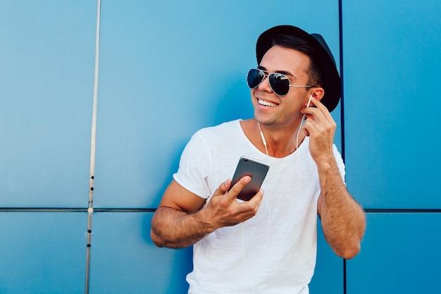 Foto al aire libre de chico atractivo en gafas de sol escuchando música en auriculares