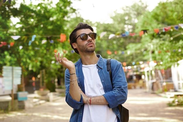 Foto al aire libre del desconcertado joven apuesto de pie sobre el verde parque de la ciudad, mirando hacia otro lado y levantando la palma, vestido con camisa azul y camiseta blanca