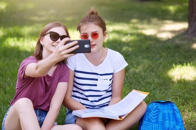 Foto al aire libre de dos hermosas hembras jóvenes sentadas en el césped en posición de loto, hace selfie en el parque, usa camisetas y pantalones cortos, gafas de sol, pasa tiempo en el patio en un caluroso día de verano.