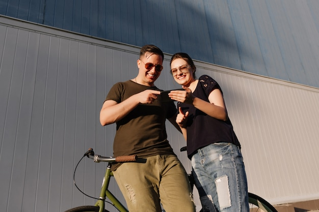 Foto al aire libre de la feliz pareja, chico joven y mujer riendo mientras mira el teléfono móvil, viendo una película divertida durante caminar con bicicleta al aire libre.