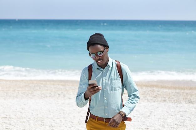 Foto al aire libre del joven afroamericano con mochila con sombrero, gafas y ropa elegante esperando su cita en pebble beach, utilizando una conexión a internet de 3g o 4g en el teléfono móvil con pantalla táctil