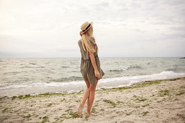 Foto al aire libre de la joven y delgada mujer rubia de pelo largo vestida con un vestido verde de verano de pie con la espalda sobre el fondo de la playa y manteniendo la mano en su sombrero