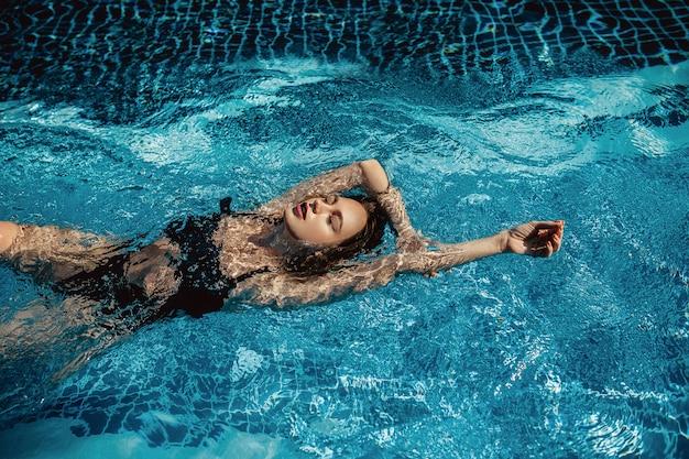 La foto al aire libre de la moda de la mujer hermosa con el pelo rubio lleva el traje de baño negro lujoso, presentando en la piscina. mujer de lujo se encuentra en la piscina cristalina