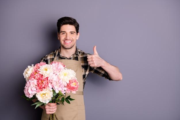 Foto de alegre apuesto hombre vestido con camisa a cuadros mostrando el pulgar hacia arriba dejando comentarios sobre la floristería pared de color gris aislado