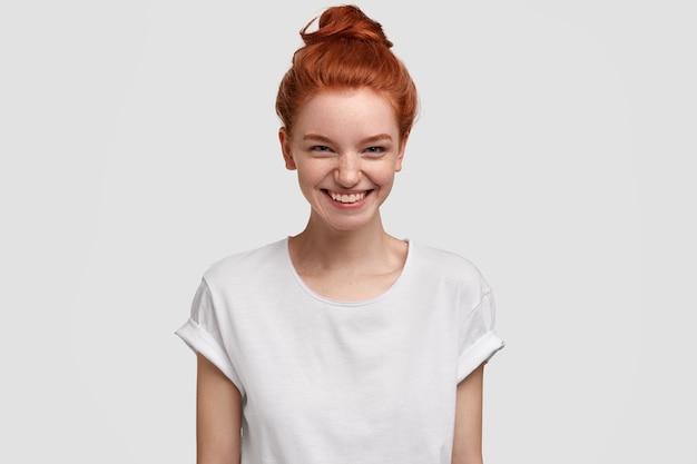 Foto de alegre encantadora adolescente pelirroja sonríe con expresión curiosa e interesada, acepta oferta maravillosa, viste camiseta blanca informal, modelos de interior