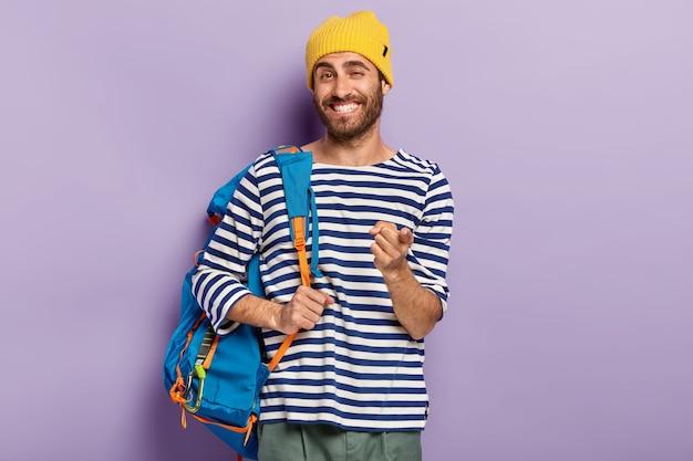 Foto de alegre hombre sonriente que el viajero le señala con el dedo índice, lleva una mochila, viste un sombrero amarillo y un suéter con rayas, expresa su elección, lo recoge, aislado en una pared púrpura