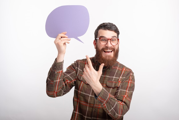 Foto de alegre joven con barba con gafas y apuntando al discurso de burbuja