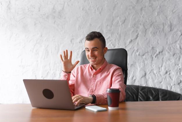 Foto de alegre joven hombre de oficina trabajando en línea y saludando a todos