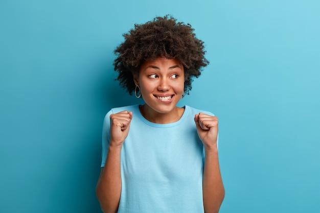 Foto de alegre mujer afroamericana aprieta los puños y espera algo agradable