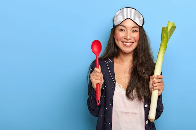 Foto de ama de casa feliz que va a cocinar un plato saludable en la mañana, sostiene el puerro verde y la cuchara roja, sonríe agradablemente, usa ropa de dormir
