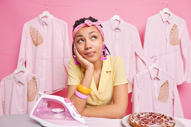 Foto de ama de casa sueña despierta sobre algo ocupado haciendo las tareas del hogar se toma un descanso después de planchar un delicioso pastel horneado vestida con ropa doméstica se inclina a bordo en la pared rosa