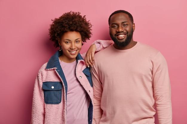 Foto de amigable mujer feliz y hombre con piel oscura de pie cerca, sonríe felizmente, usa ropa de moda en colores pastel