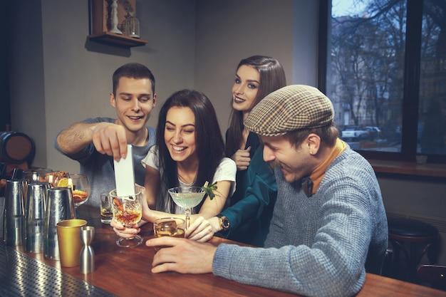 Foto de amigos alegres en el bar o en el pub comunicándose entre ellos